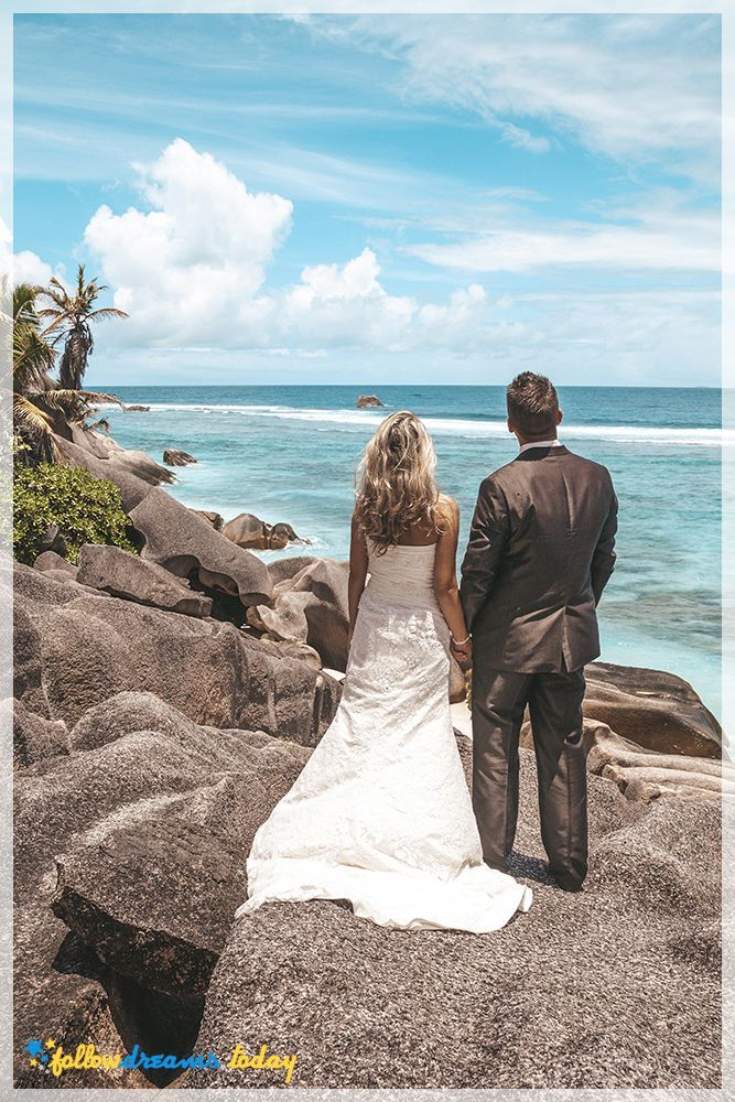 Bride and groom standing holding hands on rocks looking out over the ocean at the seashore under tropical sunshine