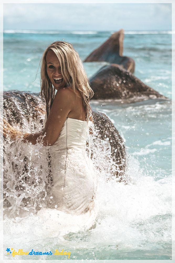 Laughing bride standing in the sea - best tropical destinations