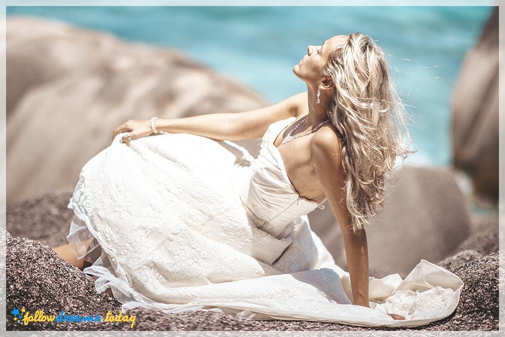 Beautiful bride taking sunbatch at stony beach at seychelles while wearing wedding dress