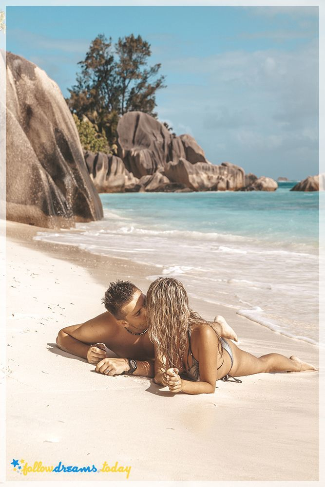 Young romantic couple laying on sandy beautiful tropical beach with turquoise water and white sand